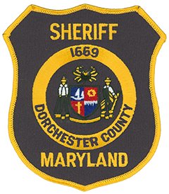 Dorchester County, Maryland, was founded in 1669 on the Eastern Shore of the Chesapeake Bay. The county's government seal, depicted on the service patch of the Dorchester County Sheriff's Office, includes a crab at the top, a waterman on the left, and a farmer on the right. These represent the county's two main sources of income: fishing and farming. Clockwise from the top left, the center shield depicts a sailboat, a cog, a display of the water and sky, and a cross. These items reflect the county's association with water sports; industry; the waterways that surround it; and, dating back to its founding, the Roman Catholic Church.