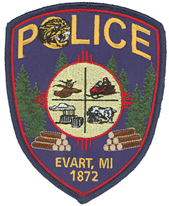 The Evart, Michigan, Police Department patch symbolizes the pride and heritage of the community it serves. The wildcat depicted at the top is the mascot of Evart High School. The center crest represents the economic strengths of the city—hunting, outdoor recreation, farming, and industry. Surrounding the crest is a tribute to Evart's once-thriving logging industry, which was largely responsible for the city's founding in 1872.