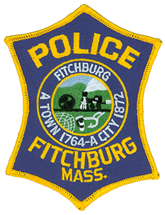 Fitchburg, Massachusetts, was incorporated in 1764 and grew through the following century to become an industrial center. The patch of the city's police department bears the unique appearance of an elongated six-pointed star. In its center is the city seal, representing the industry and agriculture that shaped Fitchburg in its early years. The seal's background depicts Rollstone Hill, which was relied upon heavily for its granite products.