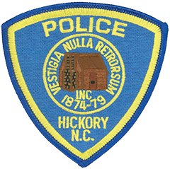 "The Hickory, North Carolina, Police Department has two service patches worn on opposite sleeves of its uniform. The left-sleeve patch features a log cabin surrounded by the Latin phrase ""Vestigia Nulla Retrorsum,"" which translates to ""Never Step Backwards."" The log cabin was known as the Hickory Tavern, and the name of the city arose from the forest of hickory trees around the tavern. The stars-and-stripes-influenced ""All-America City"" patch worn on the right uniform sleeve honors Hickory's three-time win of the National Civic League's prestigious All-America City Award in 1967, 1987, and 2007. The award was founded in 1949 to recognize cities in which citizens, businesses, nonprofit organizations, and government agencies work together to meet the community's needs and solve common problems."