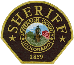 The Jefferson County, Colorado, Sheriff's Office was founded in 1859 and is the largest full-service sheriff's office in the state. The agency's service patch symbolizes its western heritage and that of Jefferson County. The black background honors fallen colleagues, the gold lettering symbolizes the gold fever that brought settlers to the area, the blue skies with clouds signify the brilliant canopy of Colorado, the red rocks represent the county's dramatic rock formations, and the mounted horseman, wearing the dark-green uniform of today's deputy sheriffs, reminds us of the challenges faced by frontier lawmen.