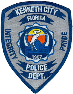 Kenneth City, Florida, was named after the young son of the local developer who founded the town in 1957. The patch of the Kenneth City Police Department depicts this year in the center below a blue outline of the town hall and a great white heron, representing the area's abundance of bird life. The surrounding dark-blue crescent symbolizes the waters of the nearby Gulf of Mexico, while the yellow and orange circle represents the rising and setting sun over those waters. Integrity and pride, the motto of the Kenneth City Police Department, is depicted along the sides of the patch.