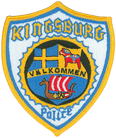 "The Kingsburg, California, Police Department patch uses the national colors of Sweden—blue and yellow—to reflect the city's rich Swedish heritage. Many of the area's settlers in the early-1870s emigrated from the Swedish province of Dalarna, origin of the Dala horse, a traditional carved and painted wooden horse statue. A Dala horse is depicted on the right side of the shield at the center of the patch—it also serves as the city's seal. On the left is the flag of Sweden, and directly below is the city's motto, ""Välkommen,"" meaning ""welcome."" The ship at the bottom of the patch represents the team mascot of Kingsburg High School, the Vikings."