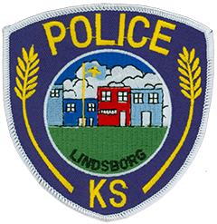 "The officers of the Lindsborg, Kansas, Police Department display two patches on their duty uniforms. On the left sleeve is the city of Lindsborg seal, prominently featuring the Dala horse. This symbol represents the city's Swedish heritage, dating back to the late-19th century when Swedish immigrants settled in the area. The right sleeve patch symbolizes the historic downtown and Old Mill Park areas of ""Little Sweden U.S.A.,"" Lindsborg's nickname. The flag of Sweden flies over the depicted community, while the wheat along the edges of the patch represents the surrounding agriculture."