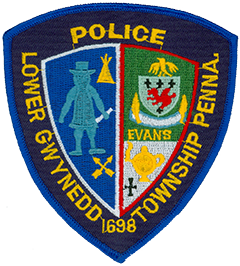 "The Quaker figure on the left side of the Lower Gwynedd Township, Pennsylvania, Police Department patch represents William Penn, the state's founder, and his influence on the town's early development. The nearby tepee stands for home and hospitality, while the crossed arrows symbolize the Delaware Indians and their friendship as the area's first occupants. The upper section of the patch's right side depicts the coat of arms and surname of the Evans family—31 of the 66 pilgrims who first arrived from Wales in 1698 held that surname. The white background in the lower section represents how Gwynedd is Welsh for ""white fields""—the pilgrims found the area blanketed with snow upon arrival. The lamp of learning honors the educational facilities in Lower Gwynedd Township, and the black cross respects the community's houses of worship."