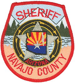 The patch of the Navajo County, Arizona, Sheriff's Office has a blood red boundary to signify the loss of Deputy Robert Varner, who was shot and killed on December 31, 1988, while attempting to stop a motorist. The black circle around the large silver star at the center of the patch represents the department's continued mourning for the lost brother. Within the circle are four gold arrows that signify the bond the sheriff's office has with three American Indian tribes—the Navajo, Hopi, and Apache—to work together for a common cause. The center of the patch shows the flag of Arizona encompassed by an outline of the state; Navajo County is depicted in silver on the right-hand side of the state. The patch's background depicts a scene of the White Mountains of Arizona above the high desert area of Monument Valley.