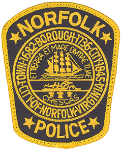 "The patch of the Norfolk, Virginia, Police Department prominently depicts the Seal of the City of Norfolk. Adopted in 1913 the seal's outer border gives a brief history of Norfolk's evolution from a town in 1682 to a borough in 1736 and then a city in 1845. The top half of the inner circle consists of a ship under full sail, typifying maritime commerce and the city's rich naval history. The bottom half depicts a field with a plow and three sheaves of wheat, representing agriculture. The Latin motto bordering the circle reads ""Et terra et mare divitiae tuae crescas,"" which translates as ""May you increase your wealth on land and sea."""