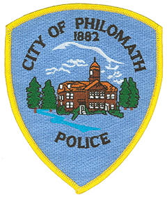 "At the center of the Philomath, Oregon, Police Department patch is the historic main building of Philomath College, today the Benton County Historical Museum. The college, open from 1865 to 1929, derived its name from two Greek words meaning ""lover of learning."" The city of Philomath grew around the campus, sharing its name, and was incorporated in 1882. Through much of the 20th century the city was a major logging and lumbering center, represented via the cluster of trees on the police department patch. Above the trees and building is a silhouette of Marys Peak, the tallest mountain in the Oregon Coast Range, located 15 miles southwest of Philomath."