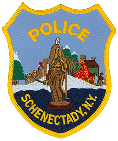 The foreground of the Schenectady, New York, Police Department patch depicts the statue of Lawrence the Indian located in the city's historical Stockade District. A member of the Mohawk tribe, Lawrence encouraged the people of Schenectady to rebuild following the 1690 massacre that nearly destroyed their settlement. The background of the patch depicts this attack, showing a group of Indian raiders outside the stockade on the left and a family of settlers with their house ablaze on the right.