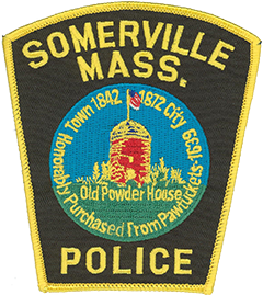 The patch of the Somerville, Massachusetts, Police Department gives a glimpse into the long and storied history of the city it serves. The innermost portion of the city's seal is featured—at its center is the Old Powder House, the oldest stone building in Massachusetts. Built around 1703 as a windmill, it went on to hold the largest supply of gunpowder in the colony and in 1774 was the site of one of the first hostile acts of the Revolutionary War. Beneath the structure is a reference to the area's purchase from the Pawtucket Indians in February 1639. Somerville was part of Charlestown—the oldest neighborhood in Boston—until 1842, at which point it separated to become a town of its own. Thirty years later, Somerville was incorporated as a city due to its growing population and increasing industrialization.