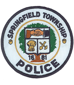 Springfield Township in Montgomery County, Pennsylvania, is one of nine townships statewide with the same name—one of these, in neighboring Delaware County, is only 22 miles away. The service patch of the Springfield Township Police Department depicts the official township seal, adopted in 1976 and worn by local officers ever since. The center of the patch features an outline of the Penn family shield; inside, the hand of William Penn, on the right, is shown linked in friendship with that of an American Indian, on the left. A sheaf of wheat is depicted in the lower left, representing early farming and the milling industry. The crossed shovel and pick in the lower right signify lime and iron ore quarrying. Behind the shield is the Penn Oak Tree, which stood in the area for 339 years until December 10, 1975. The township's founding year, 1681, is featured at the base of the tree.