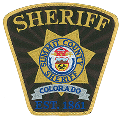 "The Summit County, Colorado, Sheriff's Office was established in 1861 by a local gold prospector who doubled as sheriff. Located in the county seat of Breckenridge, the sheriff's office today has 73 employees across five divisions. Its service patch features a seven-point gold star with the Colorado State Seal in the center. At the top of the seal is the ""Eye of Providence,"" enclosed by a triangle emanating rays. Below the eye is a Roman fasces—a bundle of rods and a battle ax bound together—along with a heraldic shield. The top half of the shield depicts three snow-capped mountains with clouds above them; the lower half shows a pick and sledgehammer crossed on a gold background. The scroll at the bottom features the state motto, Nil sine numine, meaning ""Nothing without the deity."""