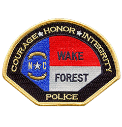 The patch of the Wake Forest, North Carolina, Police Department prominently displays the state flag in its center bordered by the department's core values—Courage, Honor, and Integrity. The black background with gold trim and lettering are recent changes brought about to match the redesign of the department's service vehicles. In 2012, the department won the grand prize in the International Police Vehicle Design Contest sponsored by Law and Order magazine.
