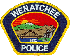 The patch of the Wenatchee, Washington, Police Department prominently features the sun setting over Mission Ridge, a skiing destination in the Cascade Mountains. Directly adjacent are the weathered rock towers of Saddle Rock, a popular local landmark. The Columbia River, which borders the city, is depicted in the foreground along with the Senator George Sellar Bridge and the Riverfront Park bike-loop trail. The year Wenatchee was incorporated, 1892, is shown at the bottom of the scene.