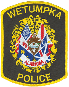 "The crest of Wetumpka, Alabama, is displayed on the service patch of the city's police department. The arrowhead at the center represents the city's early American Indian heritage, as does the face directly above. The city's name comes from a Creek Indian word meaning ""rumbling waters,"" a reference to the nearby rapids in the Coosa River. Within the arrowhead, the river is shown below the historical Bibb Graves Bridge. Also shown is a fleur-de-lis, representing Wetumpka's French settlement from 1714 to 1763. Surrounding these symbols are the six flags under which the city was historically governed."