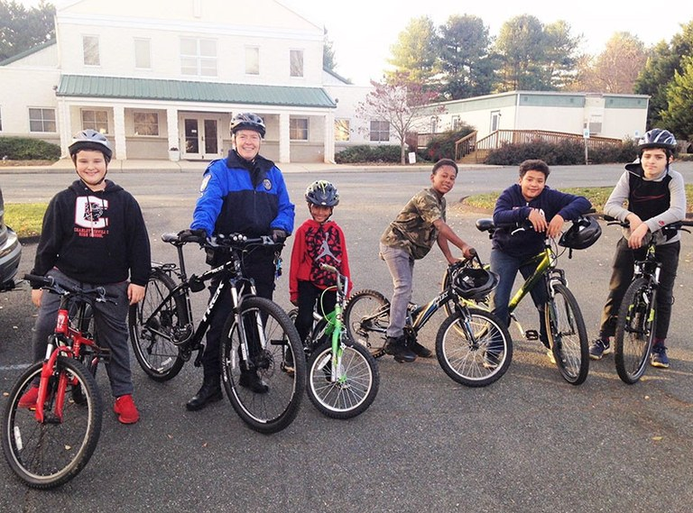 An image of a Charlottesville, Virginia, police officer with children from the community participating in the Pedal Power Community Outreach Program.