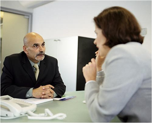 Stock image of a manager talking with an employee in an office.