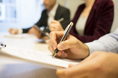 Stock image of a person taking notes in a meeting with two other people.