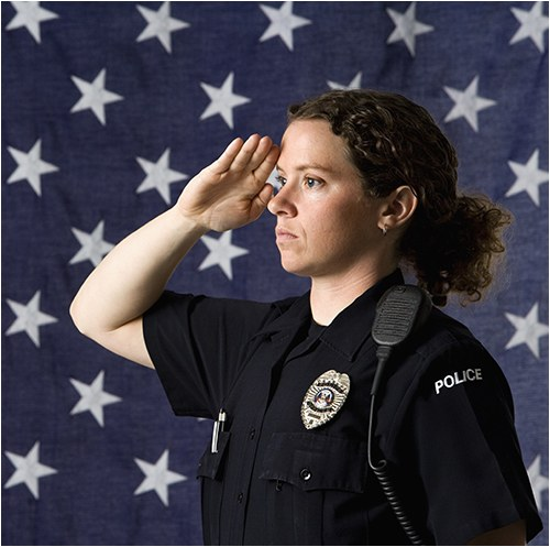 A female police officer salutes with an American flag in the background.