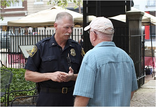 A police officer talks to an elderly man on the street.