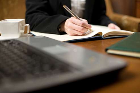 A leader is depicted taking notes in an office setting.