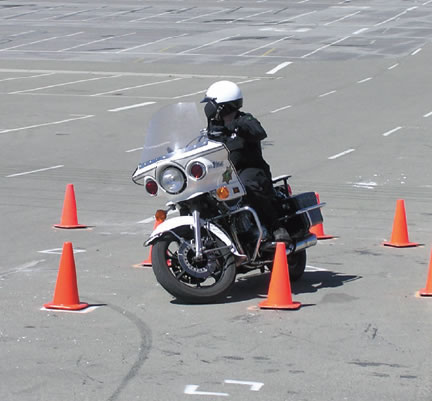 A motorcycle cop practices his maneuvering skills in a parking lot with traffic cones.