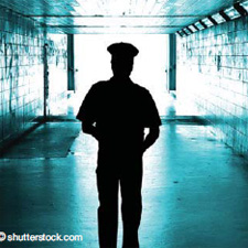 Depiction of an officer's silhouette in an empty hallway.