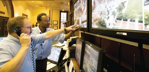 Two Men Watching Surveillance Camera Screens