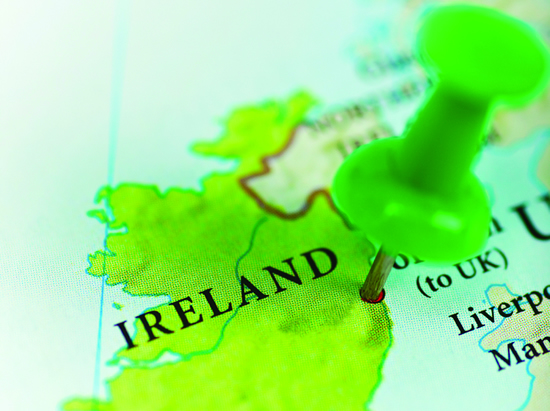 A depiction of Ireland on a map with a tack inserted above it.