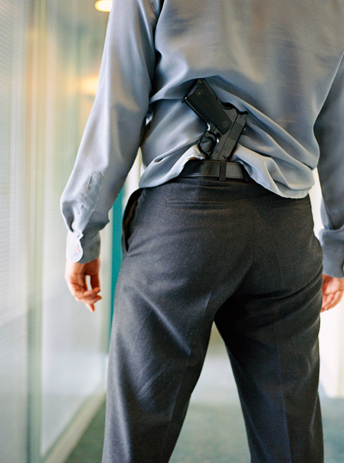 Stock image of a man with a gun under his belt.