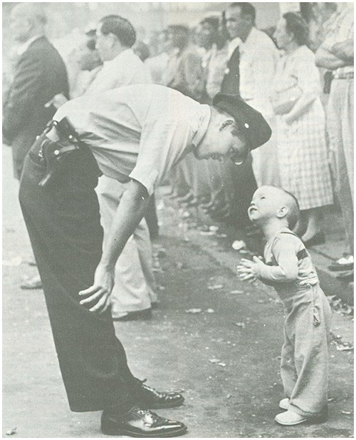 A young boy meets a friendly policeman. This photograph, depicting one glimpse of the daily duties of one police officer, portrays a moment in law enforcement and public relations.