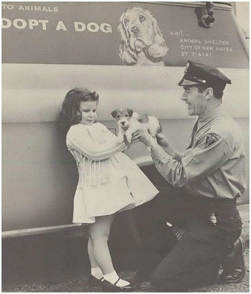 """This photo appeared in the August 1965 issue in an article titled """"Improve Your Department's Image—With a Good Annual Report."""" The caption read, """"Information relating to humane treatment of animals and the department's work with children adds appeal and public interest to annual reports."""""""