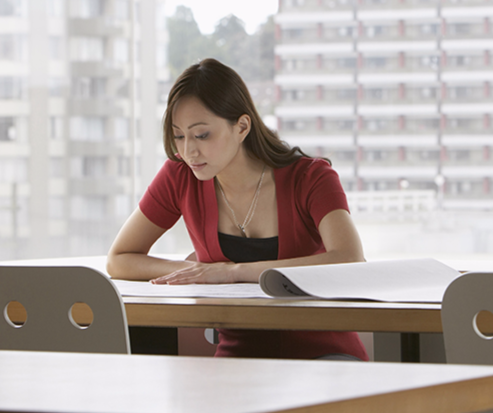 Stock image of a young woman looking at a document.