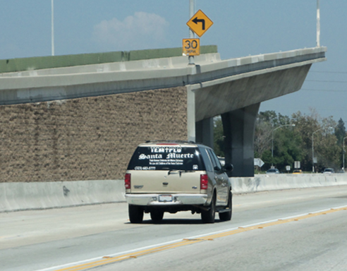 A vehicle with Santa Muerte lettering on the rear window driving down a highway. Photo provided by Pamela L. Bunker.