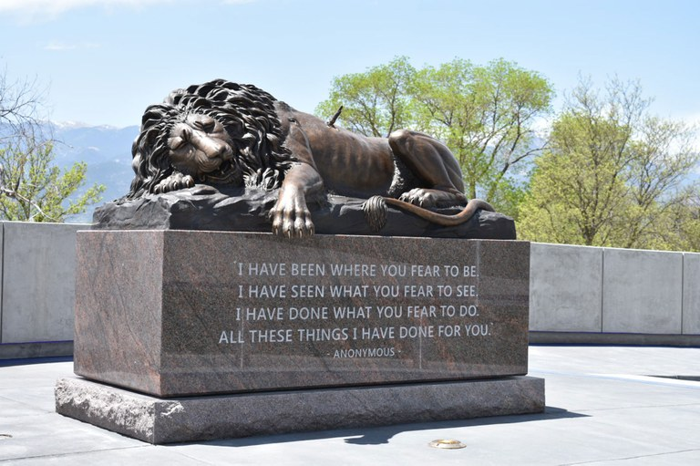 Photo of the Pikes Peak Region Peace Officers' Memorial of a fallen lion upon a base of granite.
