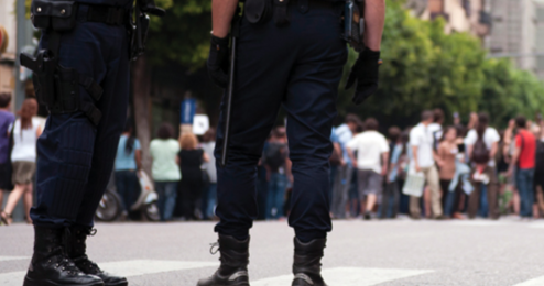 Two police officers are depicted from the waist down providing crowd management at an event. © iStockphoto.com.
