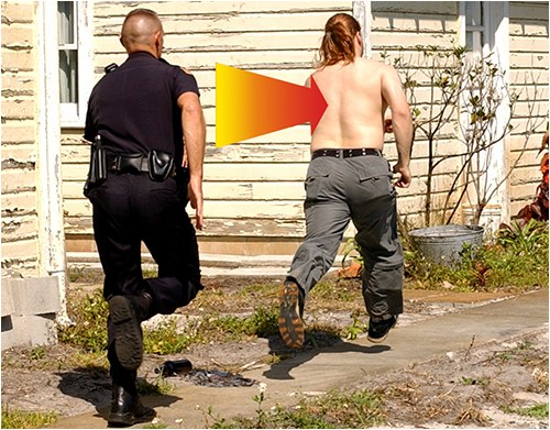A police officer chases a shirtless suspect on foot.