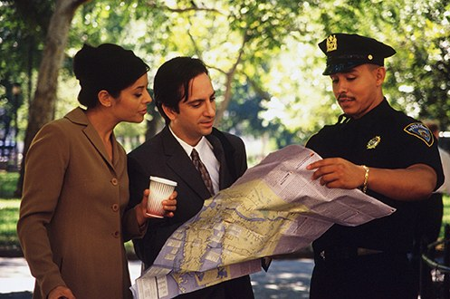 A police officer shows two citizens a location on a map.
