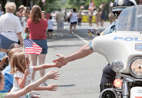 A police officer on a motorcycle reaches out waving kids at a community parade.