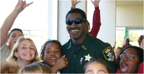 A smiling police officer with a group of kids. © R. Rossi / Sarasota Sheriff's Office.