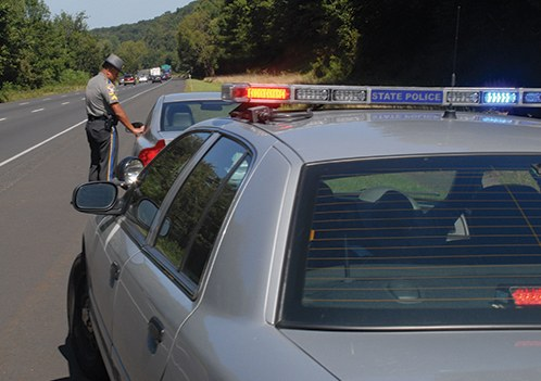 Stock image of a state police officer standing next to a car that he has pulled over on the side of a highway.