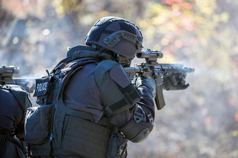 A stock photo of a police officer in heavy gear and shooting a semi-automatic weapon.