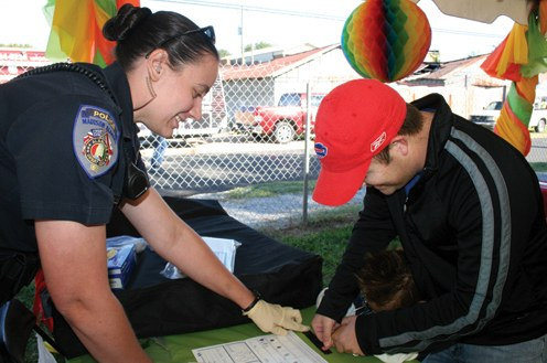 Smiling police officer taking the fingerprints of a member of the public. © Debbie Overcash