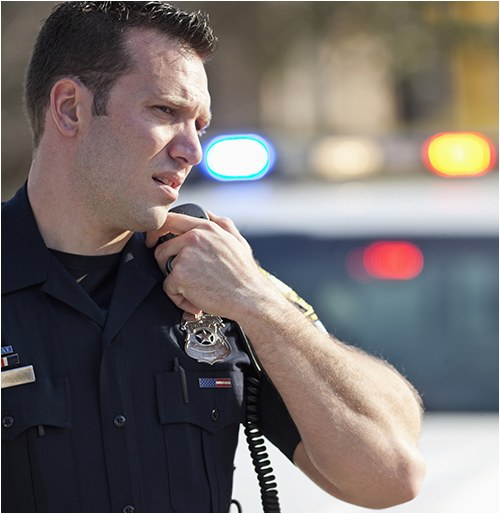 Stock image of a police officer talking into a microphone with a police vehicle in the background.