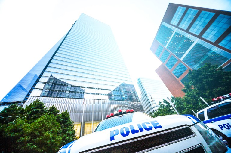 A stock image of police vehicles in front of an office building.