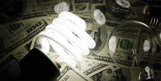 Hundred-dollar bills are enlightened by an energy-efficient light bulb.