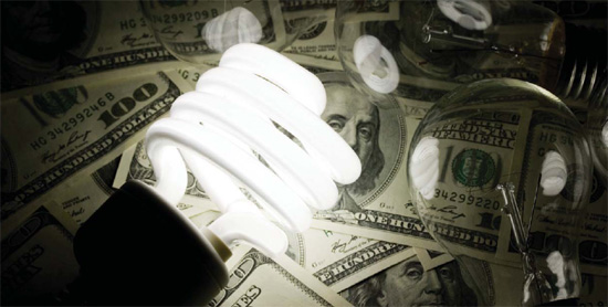 Hundred-dollar bills are enlightened by an energy-efficient light bulb.