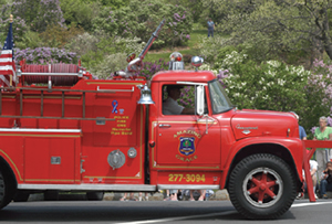 A fire truck from the late-'50s to early-'70s is depicted at a community event.