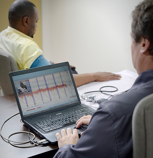 Stock image of a man at a computer performing a polygraph exam on another man seated in a chair.
