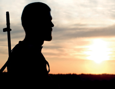 A man with a rifle looks out upon his surroundings during sunset. © shutterstock.com